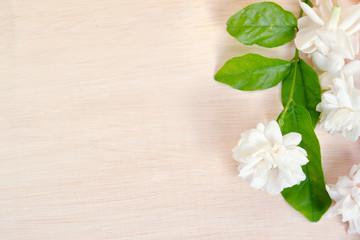 Jasmine flowers spread on wooden board background