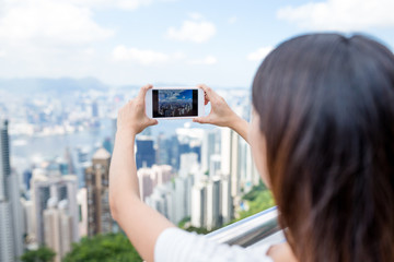 Woman taking photo with cellphone in Hong Kong
