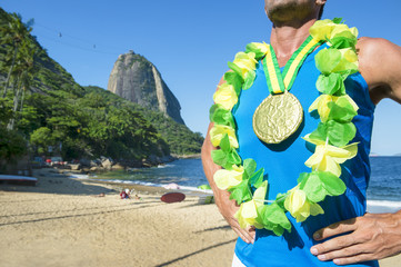 First place athlete wearing gold medal and Brazil colors lei standing outdoors in front of Sugarloaf Mountain, Rio de Janeiro