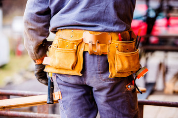 Close-up of construction worker with tool bag, rear view