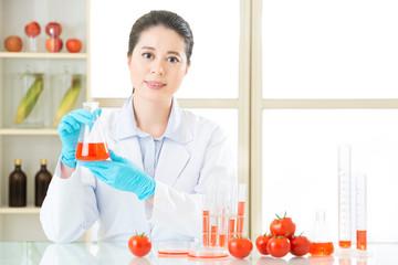 Researcher and microscope with a GMO tomato