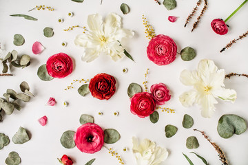 Pattern with pink and red roses or ranunculus, white tulips and green leaves on white background. Flat lay, top view