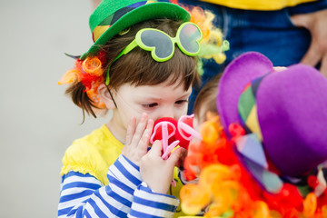 Adorable little girl ahd her sister in clown costume outdoors at summer day