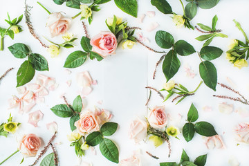 Empty paper blank with pink roses on white background. Flat lay, top view