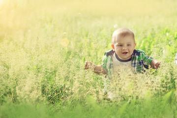 little baby boy sitting summer outdoors grass in sun