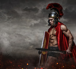 Male in spartan costume holding sword and shield.