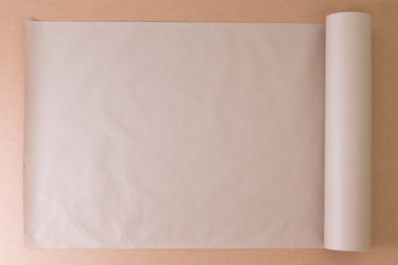 Opened roll of plain brown paper on cardboard