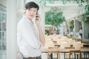 handsome asian man. businessman talking on mobile phone in moder