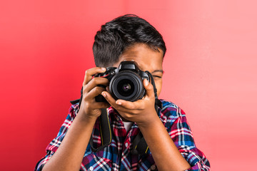 10 year old indian boy holding digital camera or DSLR camera, posing like a professional photographer, young photographer, kid photographer, child photographer, portrait, closeup, red background
