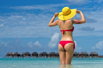 Sexy woman in hat on the tropical beach