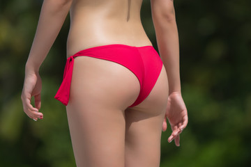 Beautiful female buttocks in bikini from the back. Sexy woman  o