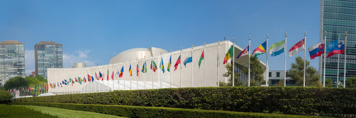UN United Nations general assembly building with world flags fly - 3:1 aspect ratio