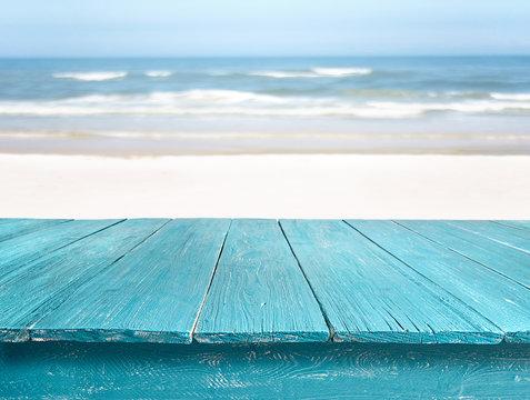 blue wooden table top against beach landscape