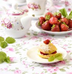 Cream puffs or profiterole filled with whipped cream,g served with strawberries