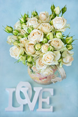 """Roses flowers in a vase and letters """"love"""" .Floral gift for a wedding or birthday."""