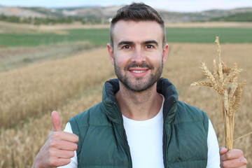 Happy handsome farmer gesturing in field ready to harvest giving a thumb up