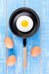 Fried egg in small pan with handle on blue wooden board