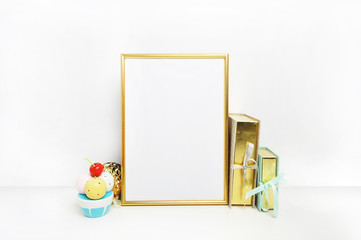Mockup frame.Gold frame and white wall. Gold book. Ice cream. Poster wall