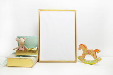 Gold frame mock-up, and white wall with toys.mouse, and mint book Place work