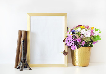 Gold frame mock-up, and white wall with gold vase, and flowers. Place work