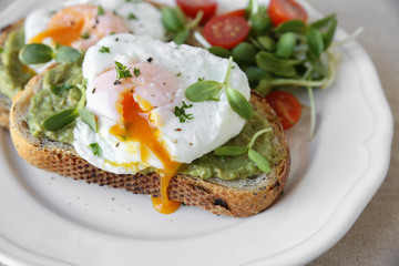 Poached eggs with avocado,tomato and sunflower sprout on sourdou