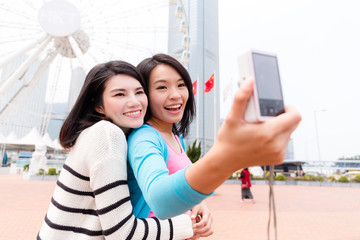 Two friends taking photo together by digital camera