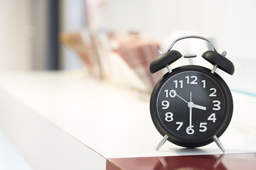 Big black alarm clock on office  background