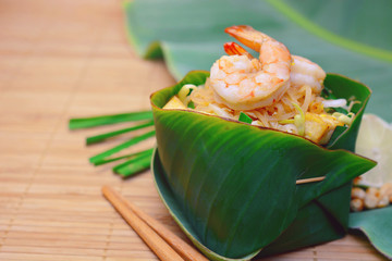 Famous traditional thai food shrimp pad thai, rice noodle stir-fry with prawns, tufu and vegetables on hand made banana leaf bowl.