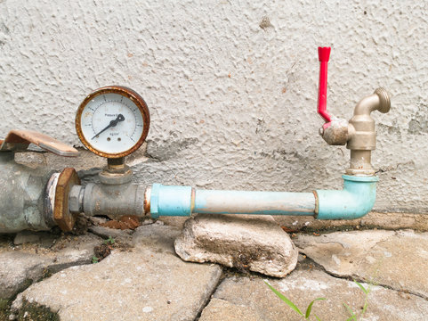 Old and rusty pressure gauge and water tap installed in strange position