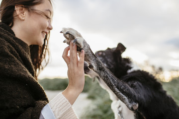 Happy young woman playing with dog on beach against sky