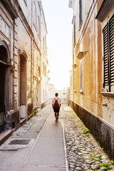 Rear view of man walking down narrow alley in old town