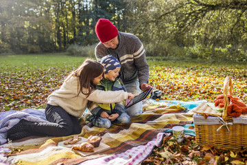Father and children using digital tablet on picnic blanket in forest