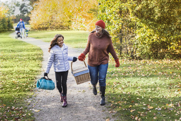Full length of mother and daughter with picnic basket walking on footpath in forest