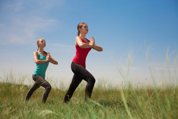 Two women doing yoga outdoors on blue sky background posing on g