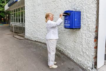 Женщина опускает письмо в почтовый