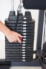 Male Hand Select Weight Of Gym Equipment. Stack Of Metal Weights Bodybuilding Equipment.