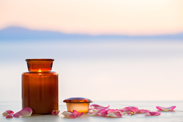 Aroma candle on sunset with rose petals