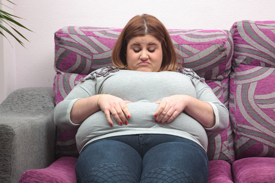 Woman touching her belly fat on the couch
