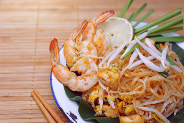 Famous traditional thai food shrimp pad thai, rice noodle stir-fry with prawns, tofu and vegetables on wooden background.