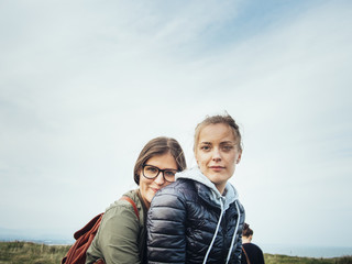 Side view portrait of affectionate female friends against sky