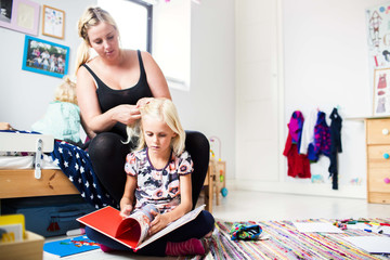 Daughter reading book while mother making her hair at home