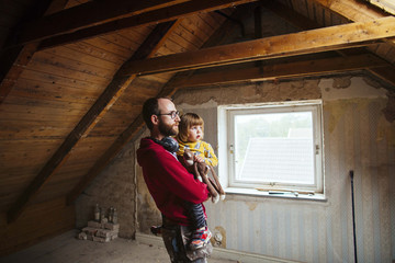 Father and daughter standing in attic under renovation