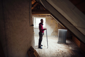 Full length portrait of man with work tool renovating attic