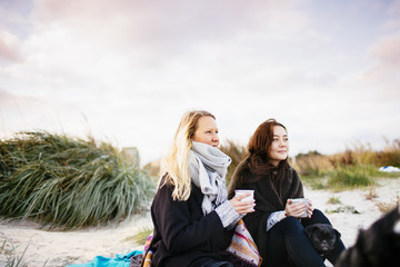 Friends holding coffee mugs while relaxing on the beach