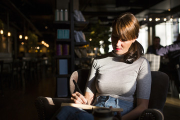 Woman sitting in cafe, writing in notepad
