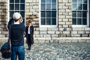 Man photographing woman standing in front of old building