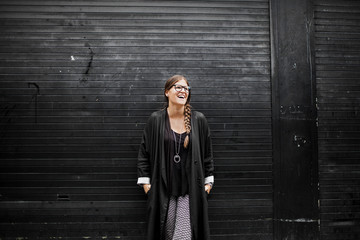 Woman standing by black wall, laughing