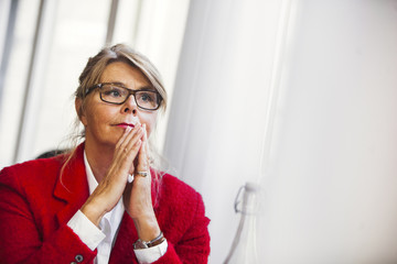 Thoughtful businesswoman with hands clasped sitting at restaurant
