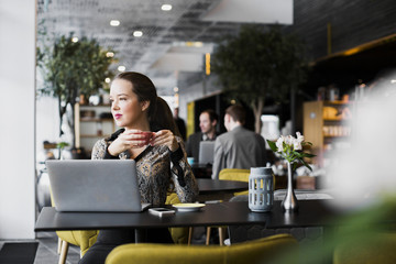 Woman sitting in cafe in front of laptop