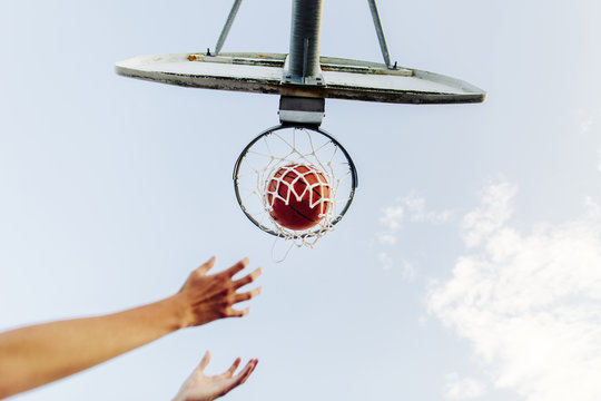 Cropped hands reaching basketball hoop against sky